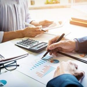 Imagem ilustrativa de pessoas realizando cálculos e análises para ilustrar o controle patrimonial de Igrejas