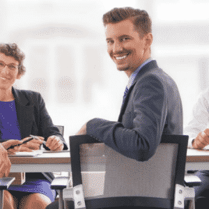 trabalhadores-ao-redor-de-uma-mesa-sorrido-para-representar-a-governanca-corporativa