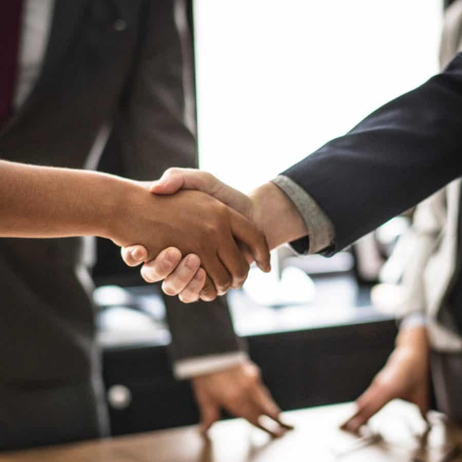 Dois empresários iniciando um Joint Venture ao apertarem as mãos