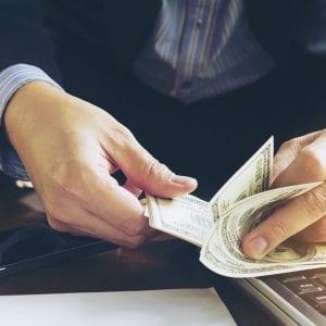 Homem contando notas de dólares para ilustrar o artigo sobre cotação do dólar
