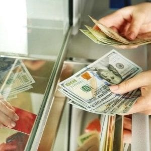 Imagem de uma pessoa com dólares na mão realizando uma transação no mercado de câmbio