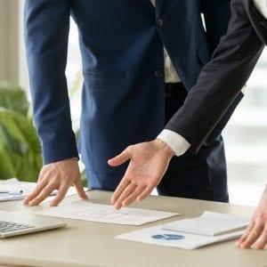 Foto de dois executivos analisando relatórios e gráficos em frente a um computador representando o serviço de uma assessoria cambial