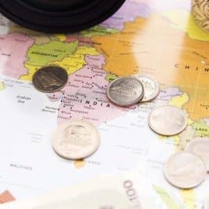 Foto de mapa mundi com notas e moedas de dólar para representar a assessoria cambial