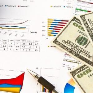 Foto de calculadora, caneta, notas de dólares e gráficos para representar o trabalho de uma assessoria cambial