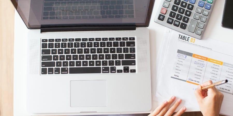 Mulher em frente a um computador com uma tabela de contas a pagar e a receber em mãos e fazendo contas para calculá-las