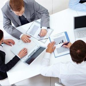 Gestores com computadores e tabelas discutindo resultados de um sistema ERP