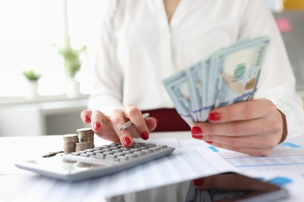 mulher com calculadora e notas bens patrimoniais