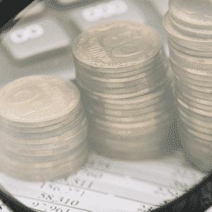 contador-realizando-fechamento-mensal-analisando-planilha-e-moedas-com-lupa