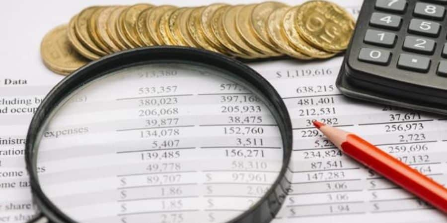 demonstracao-financeira-lupa-moedas-e-calculadoras-para-fazer-o-planejamento-tributario