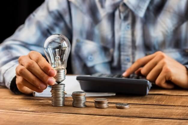 homem segurando lâmpada e calculando controle patrimonial