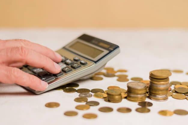 mão calculando e moedas controle patrimonial