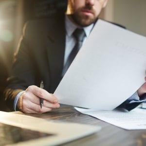 Homem de negócios analisando documentos para realizar due dilligence