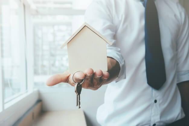 homem com casa e chave na mão aluguel de imóvel