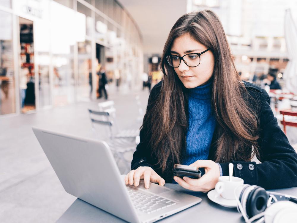 mulher com celular e notebook análise de mercado