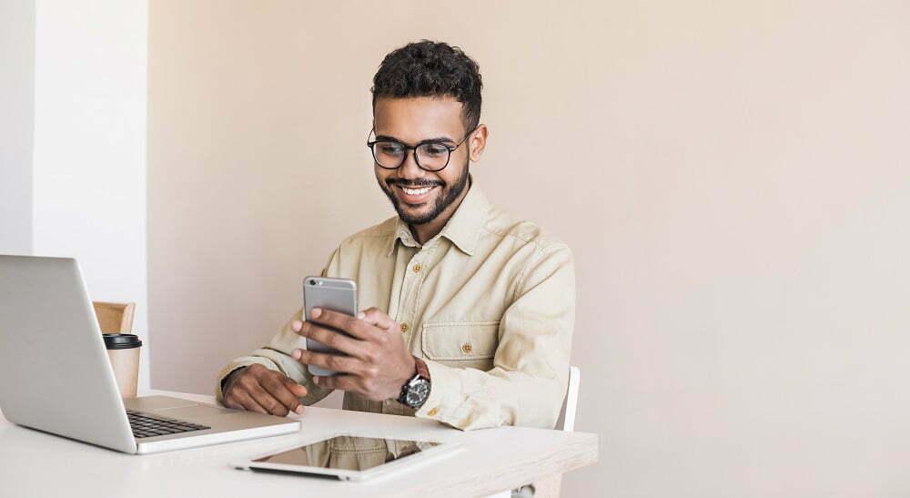 homem com celular na mão e notebook open banking